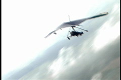 Pan to Tilt of Hang Glider Soaring Through the Clouds Stock Footage