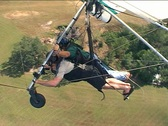 Stock Video Footage of Steady Side Shot of Two People Hang Gliding and Turning to Landing