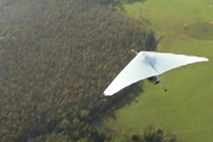 Overhead Hang Glider Swoops Through Frame Aerial Stock Footage