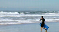 Bodyboarder Walks Out into Surf, Waves on Beach  Stock Footage