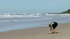 Bodyboarder Prepares to Head Out into Surf, Waves on Beach  Stock Footage