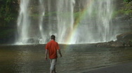 Stock Video Footage of Man and tropical waterfall with rainbow