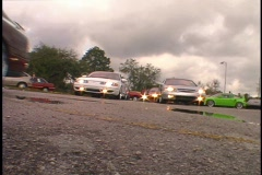 Angled View of Street Cars Leaving a Parking Lot Stock Footage