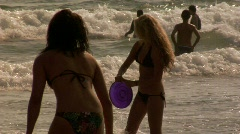 Woman throws frisbee at beach SLOW MOTION Stock Footage