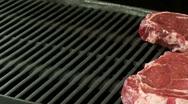 Putting rib eye steak on grill Stock Footage