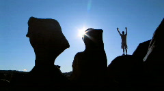 Man in silhouette with arms raised in Goblin Valley, Utah - stock footage