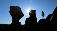 Man in silhouette with arms raised in Goblin Valley, Utah Stock Footage