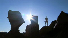 Man on rock next to hoodo in Goblin Valley in shadow Stock Footage