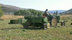 Farmer on hay baler close away M HD Stock Footage