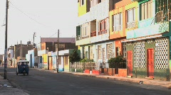 blue tuk tuks pass one another with colorful buildings in Peru Stock Footage