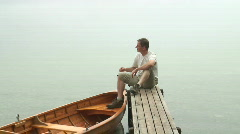 Man sitting on a landing stage Stock Footage