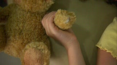 Girl's hand releases her teddy bear. - stock footage