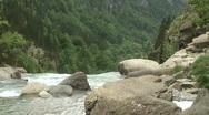 Hiker beside a mountain stream Stock Footage