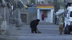 Indian woman sweeps morning streets (w/sound) Stock Footage