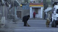 Stock Video Footage of Indian woman sweeps morning streets (w/sound)