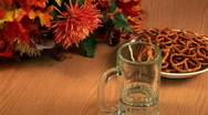 Pouring beer into a mug with pretzels and fall foliage  Stock Footage