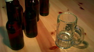 Pouring beer into a mug on pine table and bottles Stock Footage