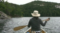 Woman paddles canoe. POV from stern. - stock footage