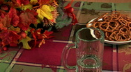 Pouring beer into mug with pretzels & fall foliage Stock Footage