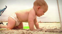 Infant toddler baby at summer beach with family playing in sand Stock Footage