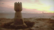 Early morning sunrise on beach with sandcastle and Jogger. Stock Footage