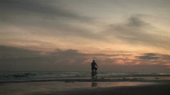Early morning sunrise on beach with Biker. - stock footage