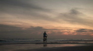 Stock Video Footage of Early morning sunrise on beach with Biker.