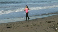 Woman Jogging on Beach Stock Footage