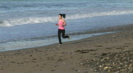 Stock Video Footage of Woman Jogging on Beach