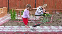 Mother with daughter cleaning home yard Stock Footage