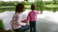 Mother with little girl on pond Stock Footage