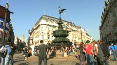 Tourists rest below the statue of Eros in Piccadilly Circus London England UK Stock Footage