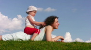 Little girl on mother on meadow Stock Footage