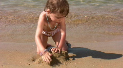 Little girl play with sand on beach Stock Footage