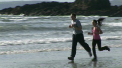 Two People Jogging along a Beach Stock Footage