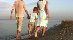 walking family with boy on beach - stock footage
