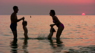 Silhouette family of four on sunset sea Stock Footage