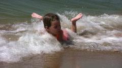 Child on splashing beach Stock Footage