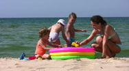 Mother with children play on beach Stock Footage