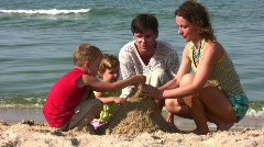Family of four play with sand Stock Footage
