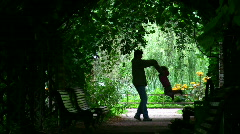 Father rotate girl silhouette in plant tunnel Stock Footage