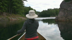 Woman paddles canoe. Rocky channel. POV from stern. - stock footage