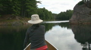Woman paddles canoe. Rocky channel. POV from stern. Stock Footage