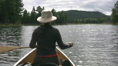 Woman paddles canoe. Sunny water. POV from stern. - stock footage