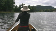 Stock Video Footage of Woman paddles canoe. Sunny water. POV from stern.