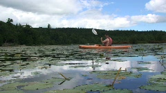 Young Male Kayaking in Lake with Lilly Pads Stock Footage