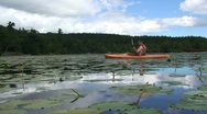 Stock Video Footage of Young Male Kayaking in Lake with Lilly Pads