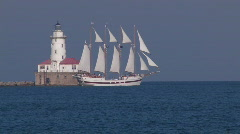 Chicago: Sailboat drifts pass a lighthouse Stock Footage