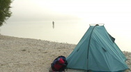 Angler in a lake with tent in the foreground Stock Footage