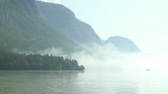 Mist clearing away at mountain lake Stock Footage
